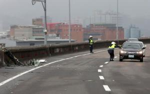 Policemen control traffic next to the wreckage of a TransAsia Airways plane which hit a motorway before crash landing in a river, in New Taipei City